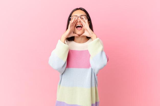 幸せを感じて、口の横に手で大きな叫びを与えるヒスパニック系のきれいな女性