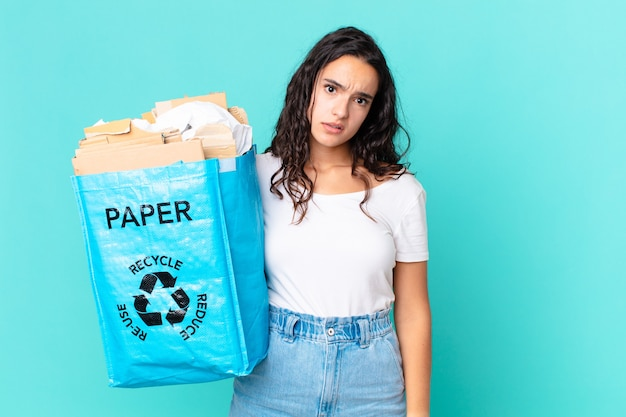困惑と混乱を感じ、再生紙袋を持っているヒスパニック系のきれいな女性