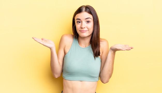 ヒスパニック系のきれいな女性が困惑して混乱していると感じ、疑ったり、重みを付けたり、面白い表現でさまざまなオプションを選択したりする