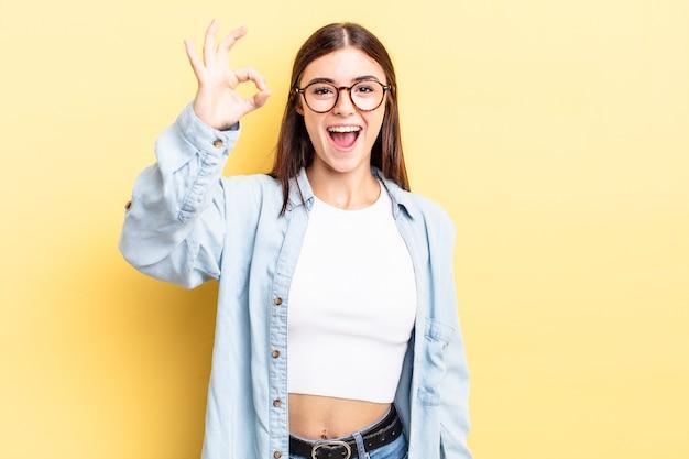 Латиноамериканская симпатичная женщина чувствует себя успешной и довольной, улыбается с широко открытым ртом, показывая рукой знак
