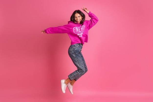 Испаноязычная красивая женщина в розовой толстовке с капюшоном и джинсах, улыбаясь, прыгает на розовом