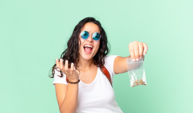 Hispanic pretty woman looking desperate, frustrated and stressed and holding a marihuana bag