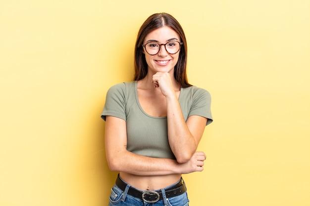 ヒスパニック系のきれいな女性は、幸せそうに見えて、あごに手を当てて笑って、疑問に思ったり、質問したり、オプションを比較したりします