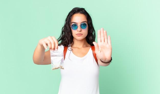 真剣に見えるヒスパニック系のきれいな女性が開いた手のひらを見せて停止ジェスチャーをし、マリファナのバッグを持っています