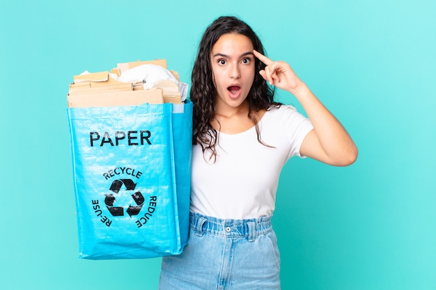 驚いたように見え、新しい考え、アイデア、または概念を実現し、再生紙袋を持っているヒスパニック系のきれいな女性