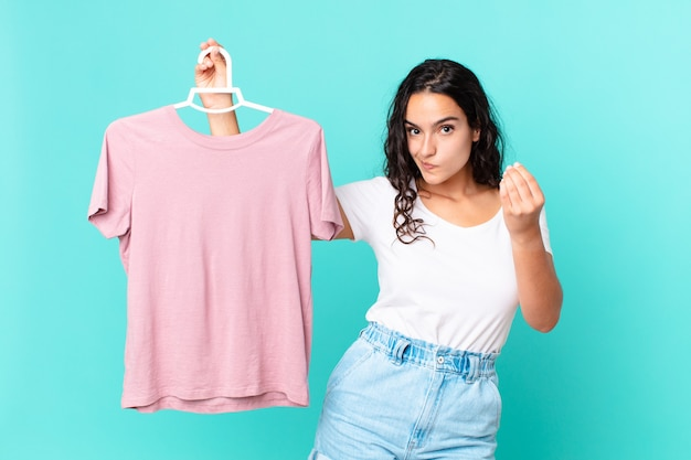 Hispanic pretty woman making capice or money gesture, telling you to pay choosing a cloth