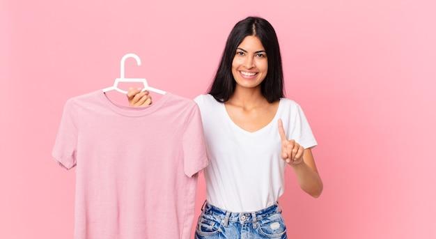 笑顔でフレンドリーに見えるヒスパニック系のきれいな女性、ナンバーワンを示し、選ばれた布を持っています