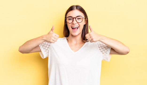 Латиноамериканская симпатичная женщина широко улыбается, выглядит счастливой, позитивной, уверенной и успешной, с двумя пальцами вверх