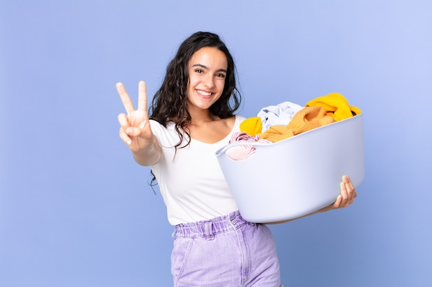 Hispanic pretty woman smiling and looking happy, gesturing victory or peace and holding a washing clothes basket