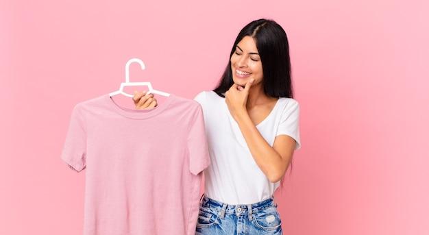 あごに手を当てて、選択した布を持って幸せで自信に満ちた表情で笑っているヒスパニック系のきれいな女性