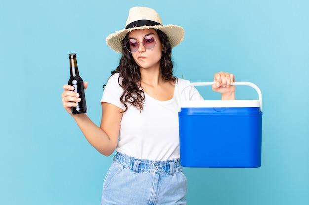 휴대용 냉장고와 맥주 병을 가진 히스패닉계 예쁜 여자
