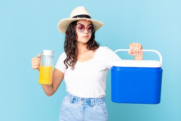 휴대용 냉장고와 오렌지 주스를 가진 히스패닉계 예쁜 여자