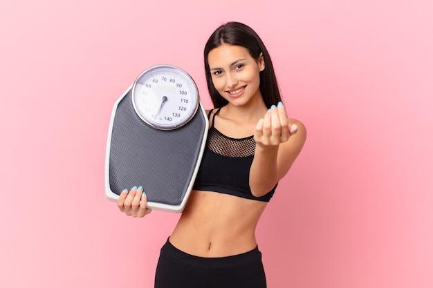 Испаноязычное симпатичная женщина с весами. концепция диеты