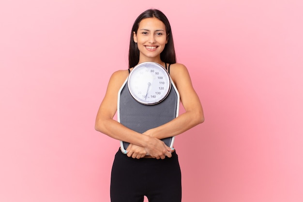 Hispanic pretty woman with a scale. diet concept