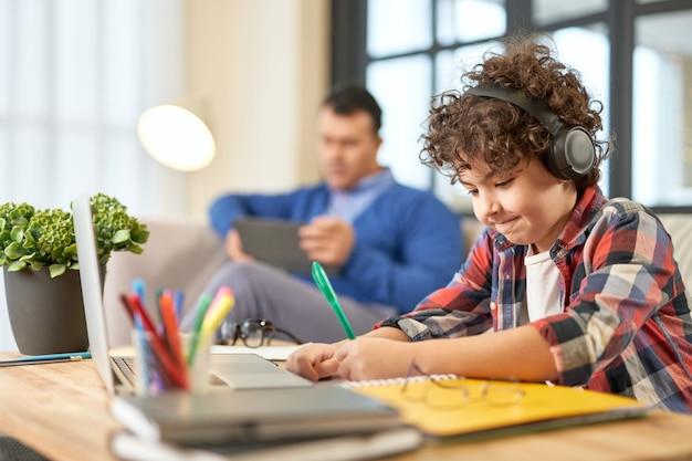 Испаноязычный школьник в наушниках готовит домашнее задание, сидя за столом у себя дома