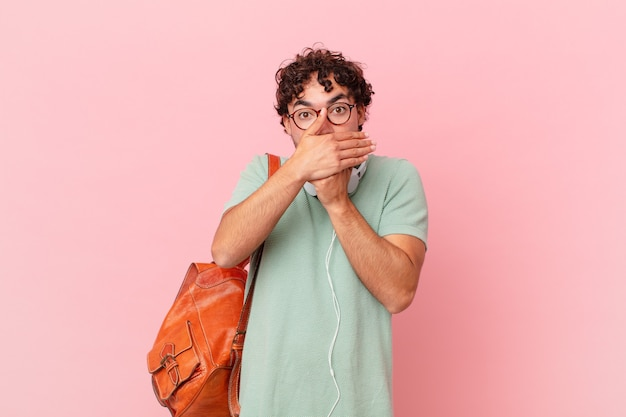 Латиноамериканский студент закрывает рот руками с шокированным, удивленным выражением лица, хранит секрет или говорит: ой