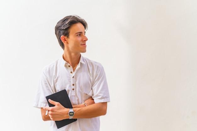 Испаноязычный студент улыбается, стоя на белом фоне с ноутбуком