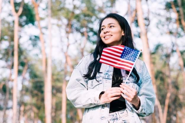 Hispanic teenage girl holding american flag on stick