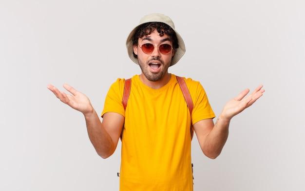 Мужчина-латиноамериканский турист чувствует себя счастливым, взволнованным, удивленным или шокированным, улыбается и удивляется чему-то невероятному