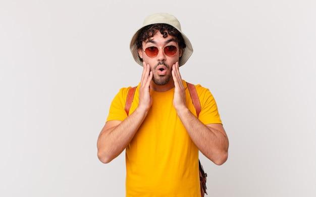 ヒスパニック系の観光客の男性は、ショックと恐怖を感じ、口を開けて頬に手を当てて恐怖を感じています