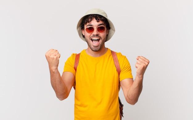 ヒスパニック系の観光客の男性は、ショックを受け、興奮し、幸せになり、笑い、成功を祝い、すごい!