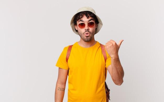 ヒスパニック系の観光客の男性は、信じられないことに驚いて、横にある物体を指差して、すごい、信じられない、と言っています。