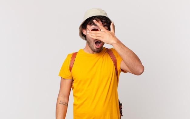 ヒスパニック系の観光客の男性は、ショックを受けたり、怖がったり、恐怖を感じたり、顔を手で覆ったり、指の間をのぞいたりしています。