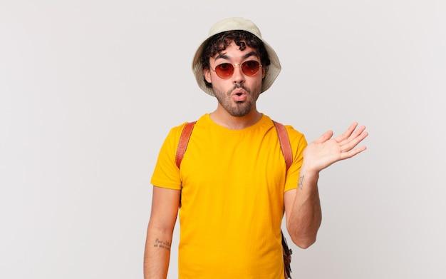 ヒスパニック系の観光客の男性は、横に開いた手でオブジェクトを保持している顎を落とし、驚いてショックを受けたように見えます