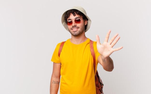 히스패닉 관광 남자 웃 고 친절 하 게 찾고, 앞으로 손으로 5 또는 5를 보여주는 카운트 다운