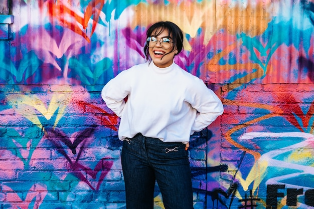 A hispanic woman cheerfully laughing with a flowered graffiti wall