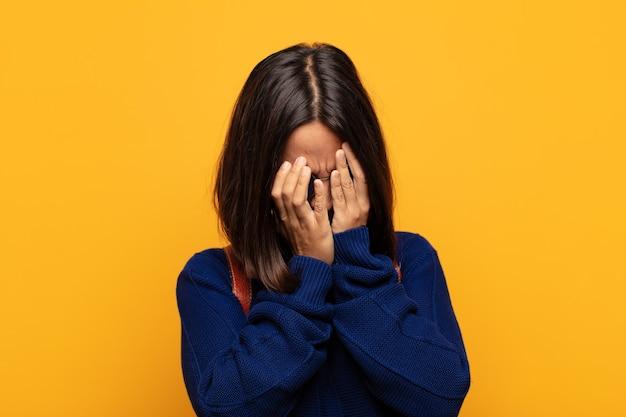 悲しくて欲求不満の絶望、泣き、側面図で目を覆っているヒスパニック系女性