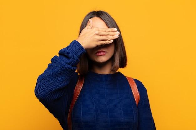 한 손으로 눈을 가리는 히스패닉계 여성이 무서워하거나 불안해하거나 궁금해하거나 맹목적으로 놀라움을 기다리고 있습니다.