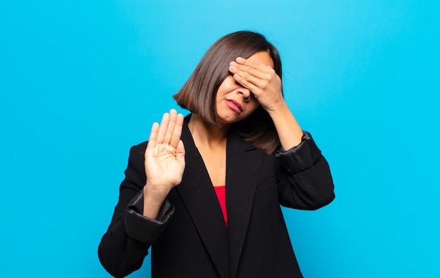 Латиноамериканка закрывает лицо рукой и выставляет другую руку вперед, чтобы остановить камеру, отказываясь от фотографий или изображений