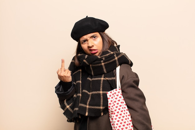 Hispanic woman feeling angry, annoyed, rebellious and aggressive, flipping the middle finger, fighting back