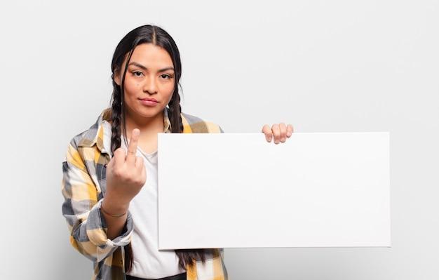 Латиноамериканская женщина чувствует себя злой, раздраженной, мятежной и агрессивной, щелкает средним пальцем, сопротивляется