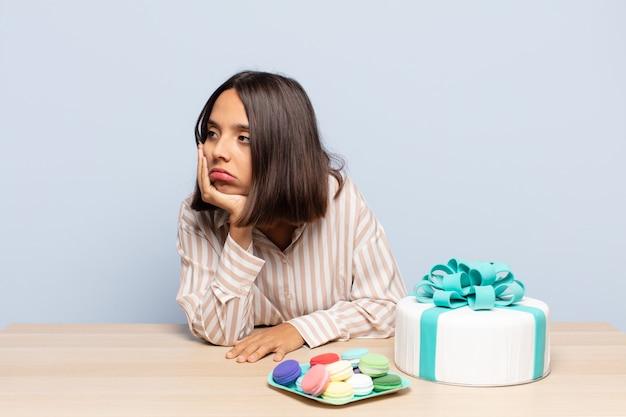 ヒスパニック系の女性は、面倒で退屈で退屈な仕事をした後、退屈で欲求不満で眠くなり、顔を手で持っています。