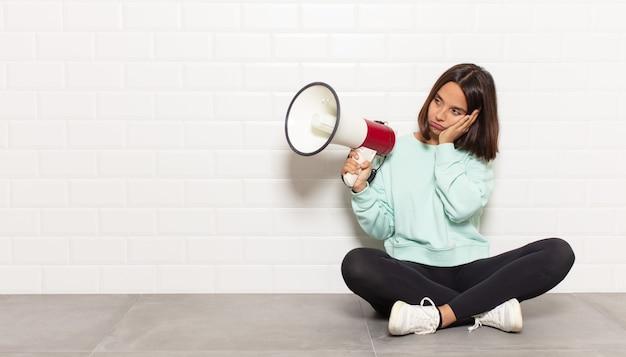 ヒスパニック系の女性は、面倒で退屈で退屈な仕事をした後、退屈、欲求不満、眠気を感じ、顔を手で持っています