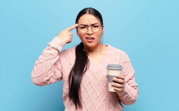 Латиноамериканская женщина смущена и озадачена, показывая, что вы сошли с ума, сошли с ума или сошли с ума