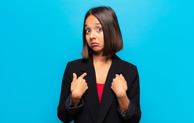 Hispanic woman feeling confused, puzzled and insecure, pointing to self wondering and asking who, me?