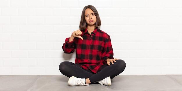 십자가, 화가, 짜증, 실망 또는 불쾌감을 느끼는 히스패닉계 여성, 심각한 표정으로 아래로 엄지 손가락 표시