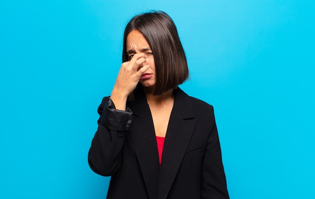 Hispanic woman feeling disgusted, holding nose to avoid smelling a foul and unpleasant stench
