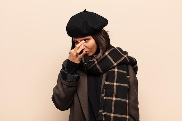 ヒスパニック系の女性は嫌悪感を感じ、悪臭や不快な悪臭を避けるために鼻を押さえています