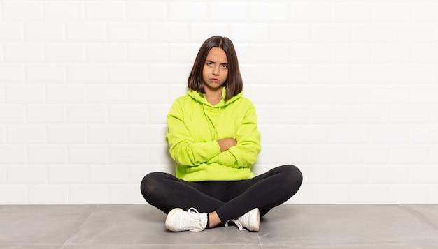 히스패닉계 여성이 불쾌하고 실망감을 느끼고 심각한 표정으로 짜증이 나며 팔을 교차