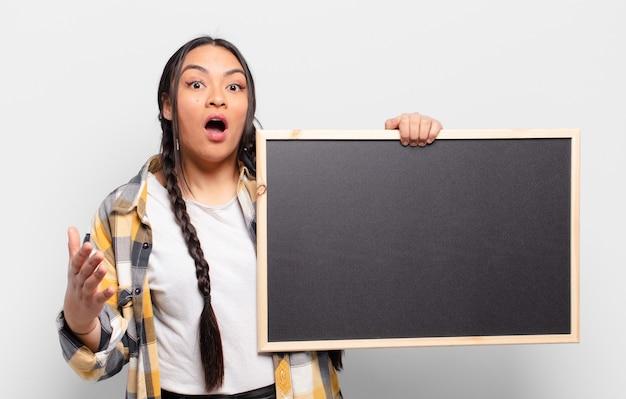 Латиноамериканская женщина чувствует себя чрезвычайно шокированной и удивленной, встревоженной и панической, с напряженным и испуганным взглядом.