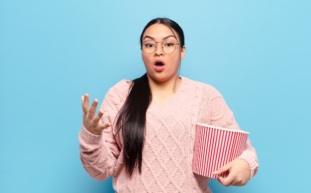 Hispanic woman feeling extremely shocked and surprised, anxious and panicking, with a stressed and horrified look
