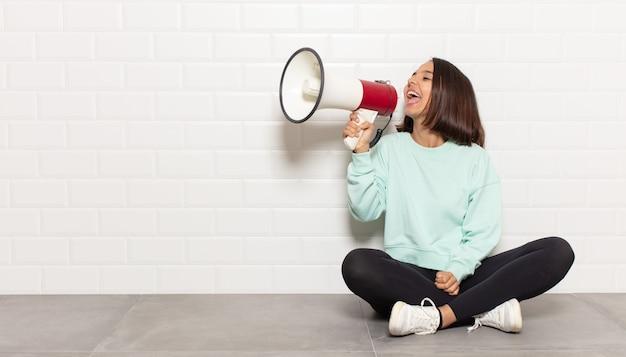 히스패닉계 여성이 행복하고 흥분되고 긍정적 인 느낌, 입 옆에 손으로 큰 소리를 지르고 외침