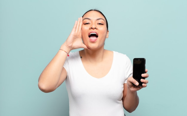ヒスパニック系の女性は、幸せ、興奮、前向きに感じ、口の横に手を置いて大きな叫び声を上げ、声をかけます