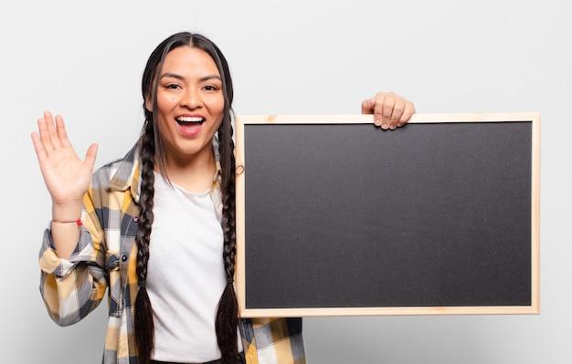 Латиноамериканская женщина чувствует себя счастливой, взволнованной, удивленной или шокированной, улыбается и удивляется чему-то невероятному