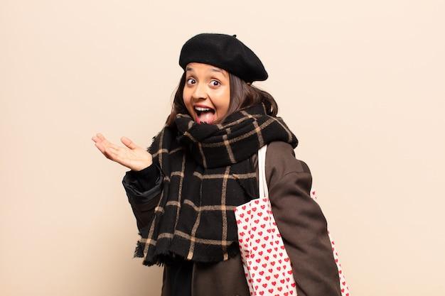 ヒスパニック系の女性は、信じられないほどの何かに幸せ、興奮、驚き、またはショックを受け、笑顔で驚いています
