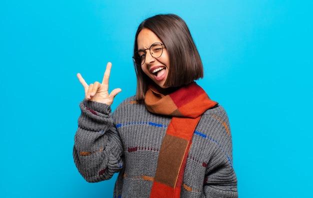 ヒスパニック系の女性は、幸せで、楽しく、自信があり、ポジティブで反抗的で、ロックやヘビーメタルのサインを手で作る